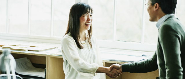 Businesswoman shaking hands with her client agreeing on the deal.